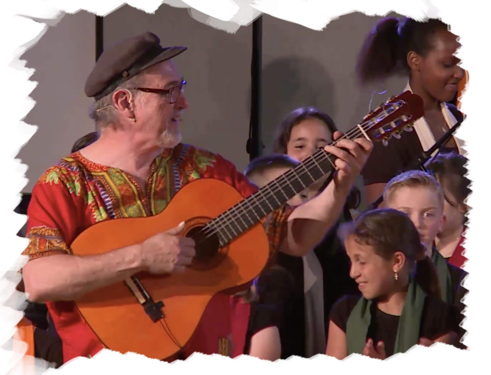 """Projet Erasmus """"Chansons et inclusion"""". Raphy et sa guitare chantent avec le choeur d'enfants de Chimay."""